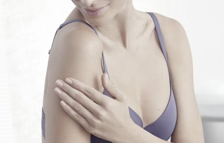 Woman wearing a bra is touching her right arm.