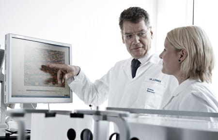 Two scientists in laboratory looking at a monitor