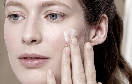 Women uses face care cream on face