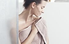 Women pats skin dry after shower
